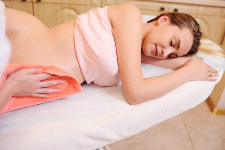 the massage therapist makes a belly massage to a pregnant woman