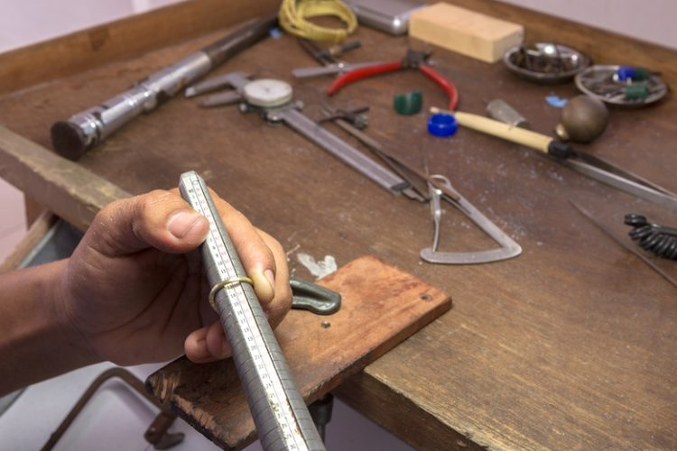 measuring the size of a ring,gold smith making