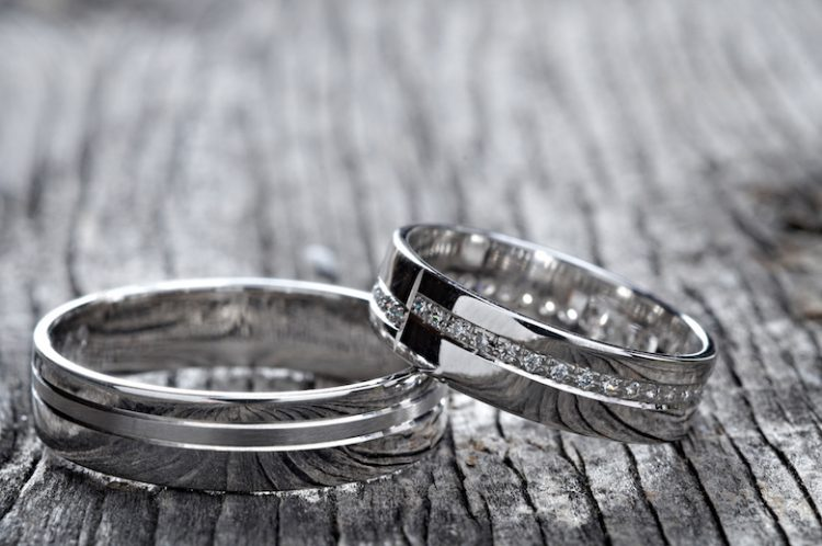 Two wedding rings on rustic wood, b&w
