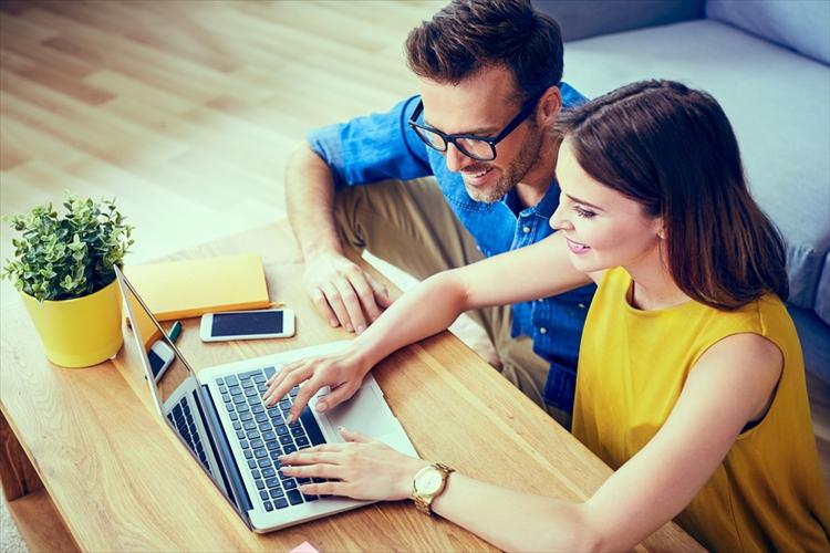 パソコンで作業するカップル