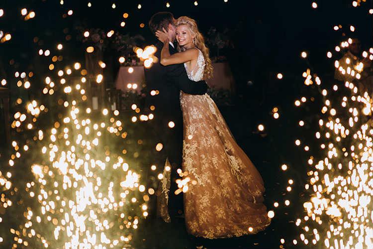 花火の中で抱き合う新郎新婦