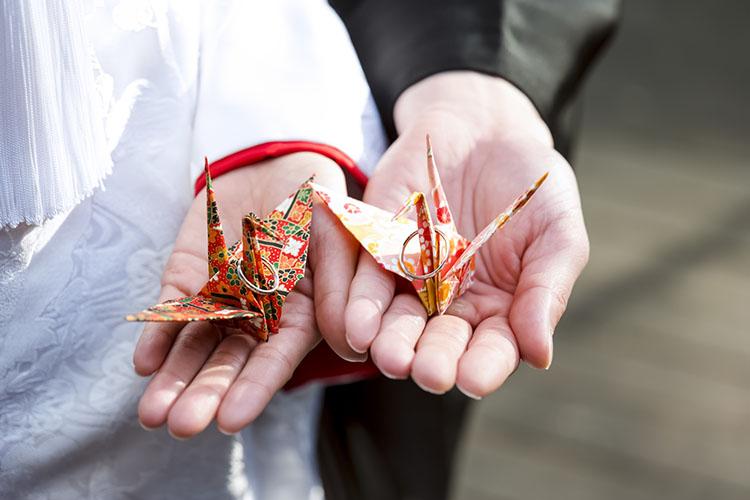折り紙の鶴を持つカップル