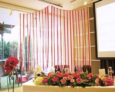 ウエディングパーティで、メインテーブル裏に設置したDIYりリボンカーテン